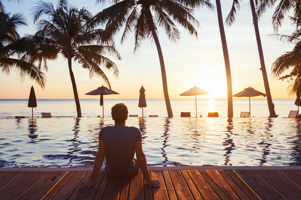 Man with feet in luxury resort pool watching the sunset over the ocean