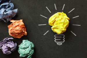 crumpled up papers with ideas, one of which turned into a light bulb - symbolize design thinking process