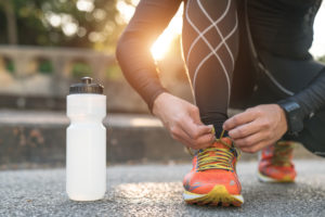 person bending down to tie up shoes next to water bottle – health benefits of walking
