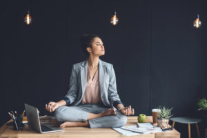 woman practicing meditation in the workplace on her desk in a tranquil black office space