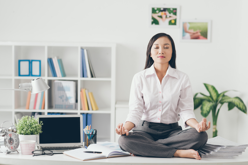 woman practicing meditation in the workplace on her desk in a tranquil white office space