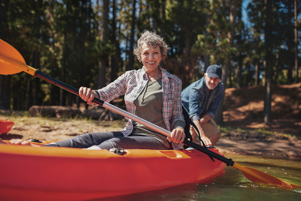 couple taking kayaks out on the lake, enjoying things to do after retirement