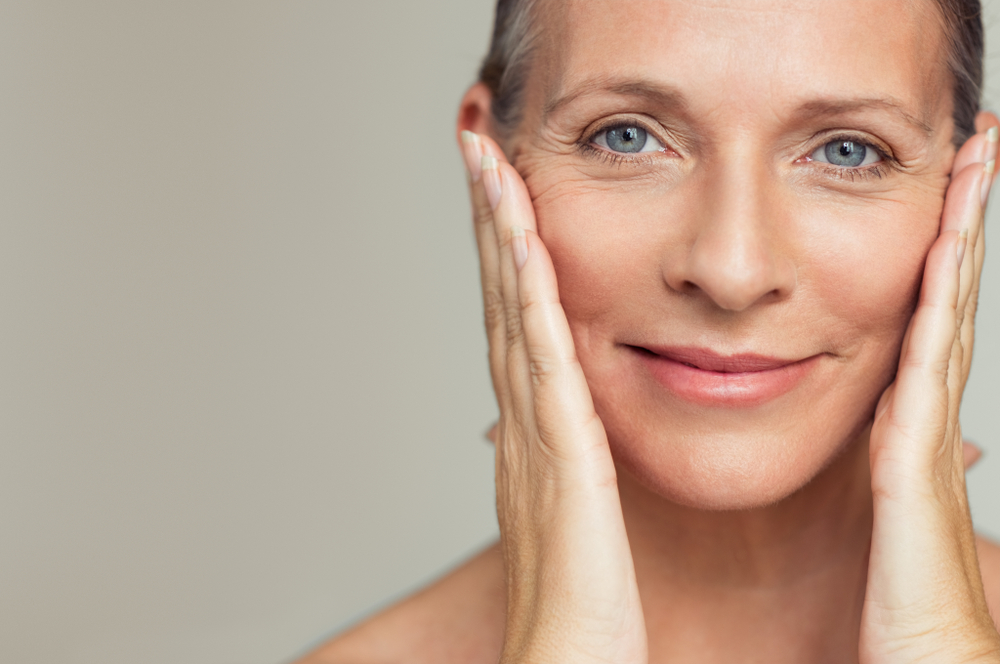 a woman pushing back the wrinkles on her face