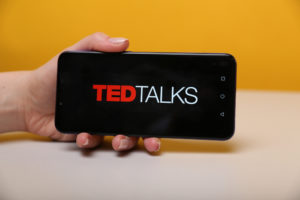 hand holding a phone with best ted talks to watch