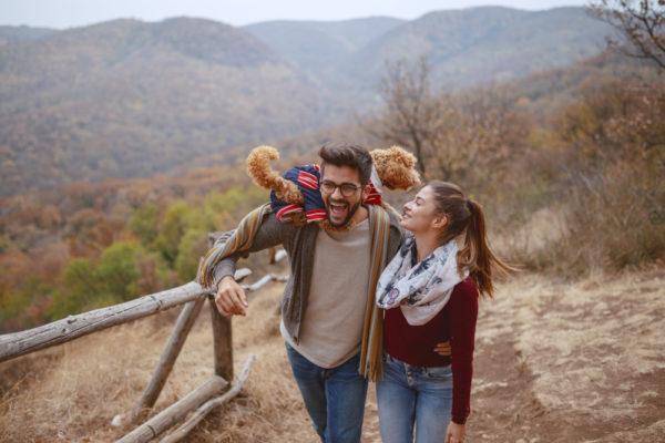 couple with dog enjoying the fall season