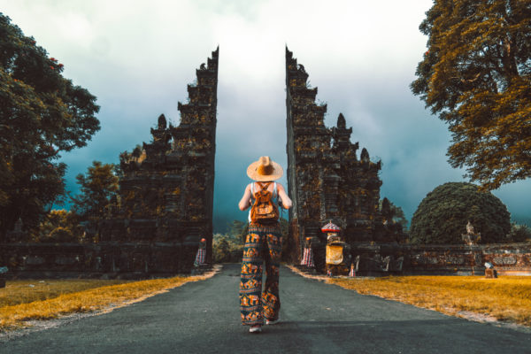 respectful tourist with backpack on vacation walking through a Hindu temple in Bali