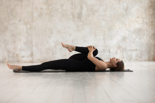 woman doing stretching exercises on yoga mat for chronic pain relief