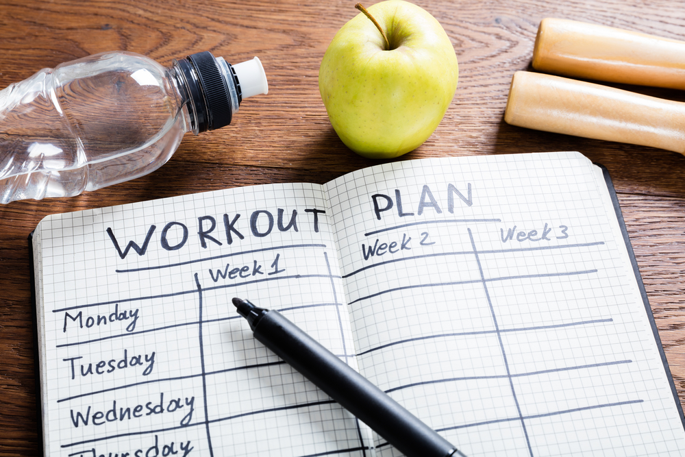 open journal that includes a weekly exercise plan for optimal health