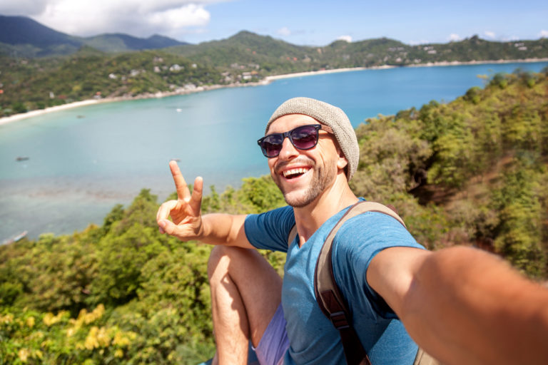 Man in a blue shirt taking a selfie with a view of an ocean behind him.