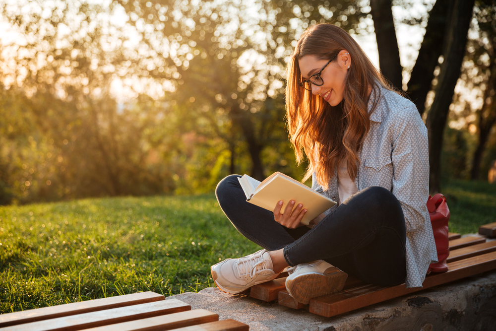 Woman reading a book outdoors.