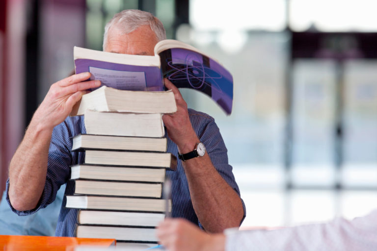 photo of a man with his face covered by an open book atop a big stack of books while he considers continuing education