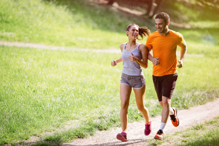 photo of a man and woman running together in a park and enjoying running benefits along the way