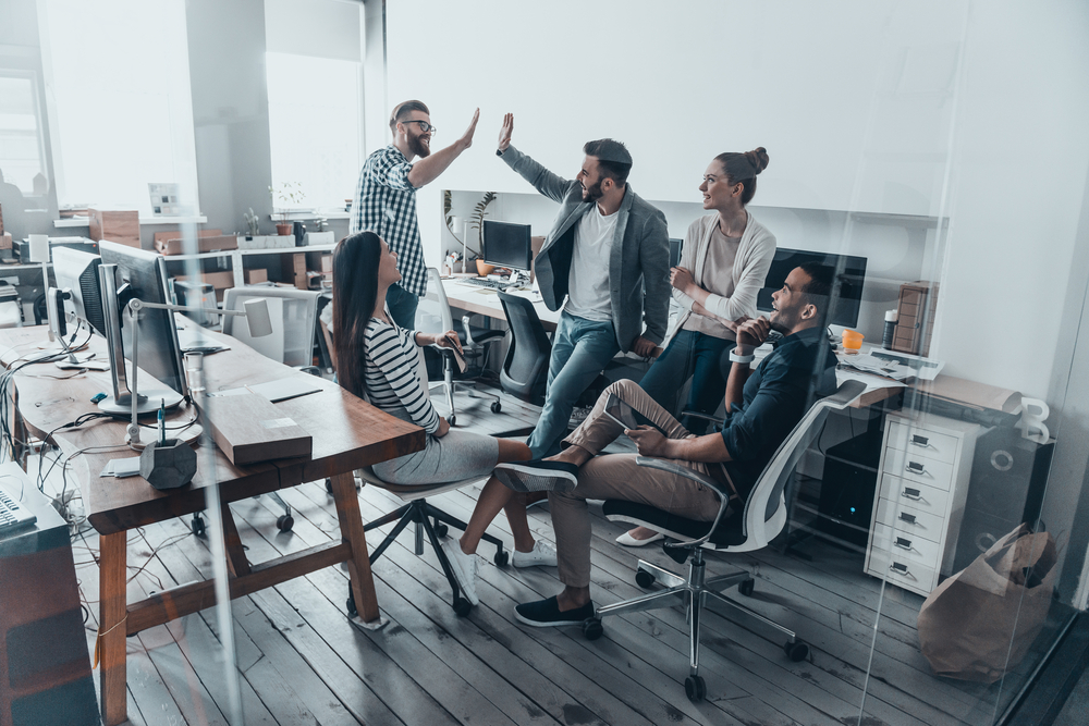 a group of five young professionals gathered together in the middle of a shared work space smiling and high-fiving each other on the 12 traits of successful people