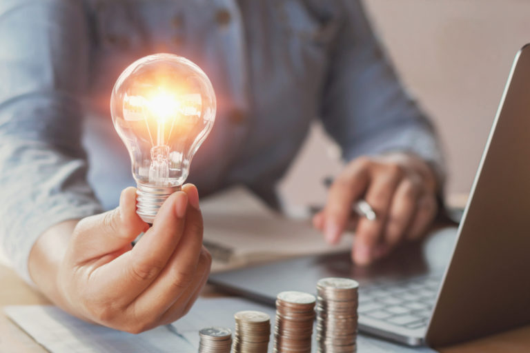 Man holding a light bulb on one hand and a pen on the other