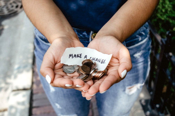 "a close-up photo of a person's two hands holding up some change with a piece of paper that says ""MAKE A CHANGE"""