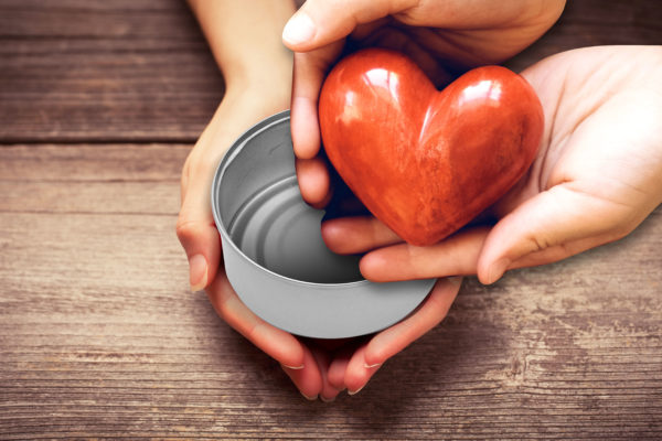 image of a pair of hands holding up an empty can while the hands of a giver place a heart-shaped offering inside it