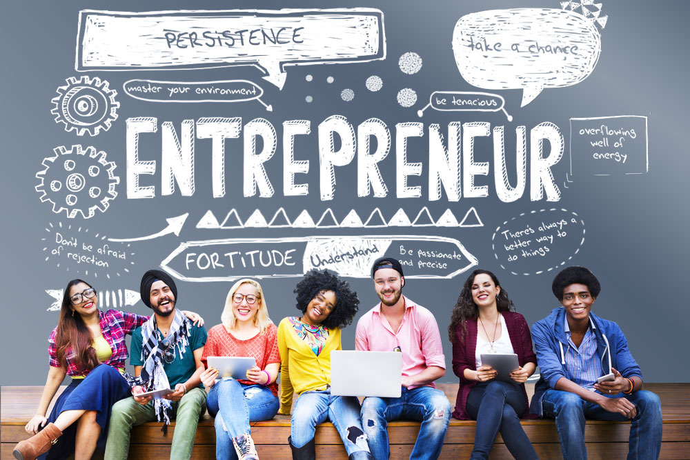 photo of seven young entrepreneurs sitting in front of a chalk mural that boasts of the traits of motivational entrepreneurs