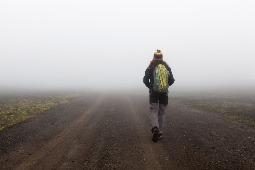 middle of nowhere, woman walking in a foggy place