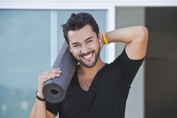 self-improvement goals man holding a yoga mat