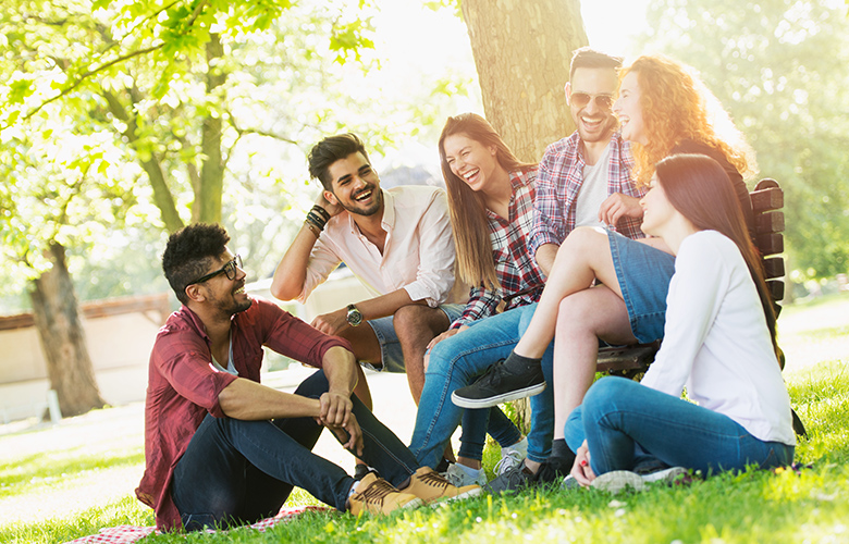 three young men and three young women seated at a park bench laughing and talking about becoming a kinder person this year