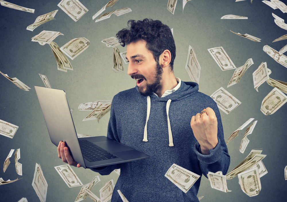 a man looking at his laptop with a fist up in victory as dollar bills fall around him as he debunks limiting money beliefs