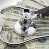 photo of a stethoscope holding down multiple US dollar bills in relation to the topic of financial health