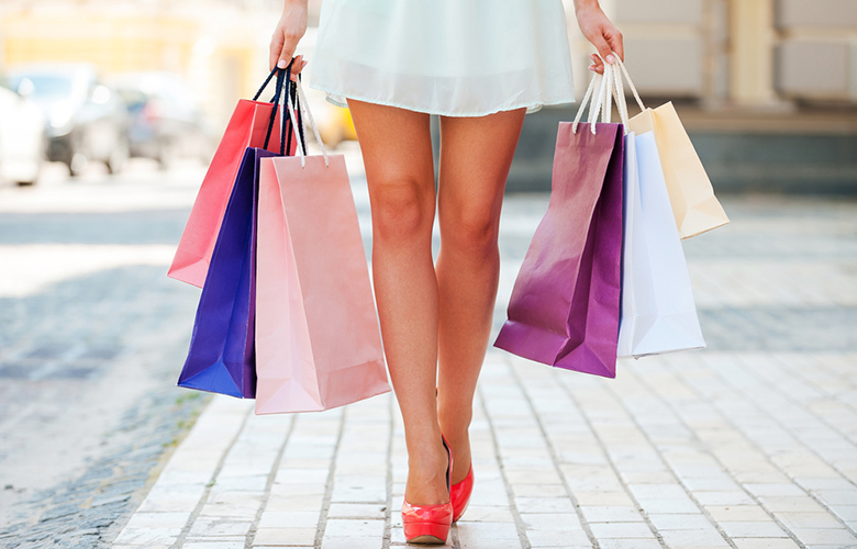 a woman in dress and heels walking down the sidewalk while holding shopping bags in relation to the topic of financial health