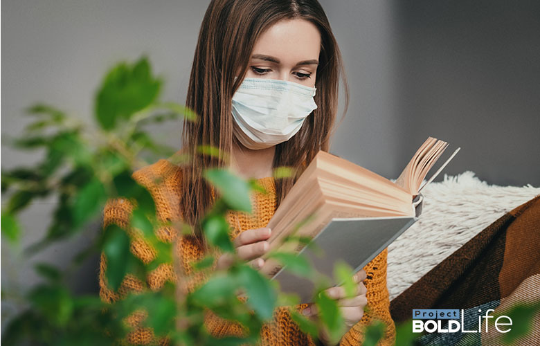 Woman in a mask reading a book