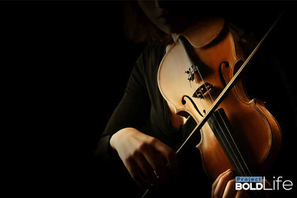 Someone in a dark room playing the violin