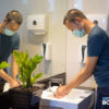 A dude washing his hands while a plant watches intently