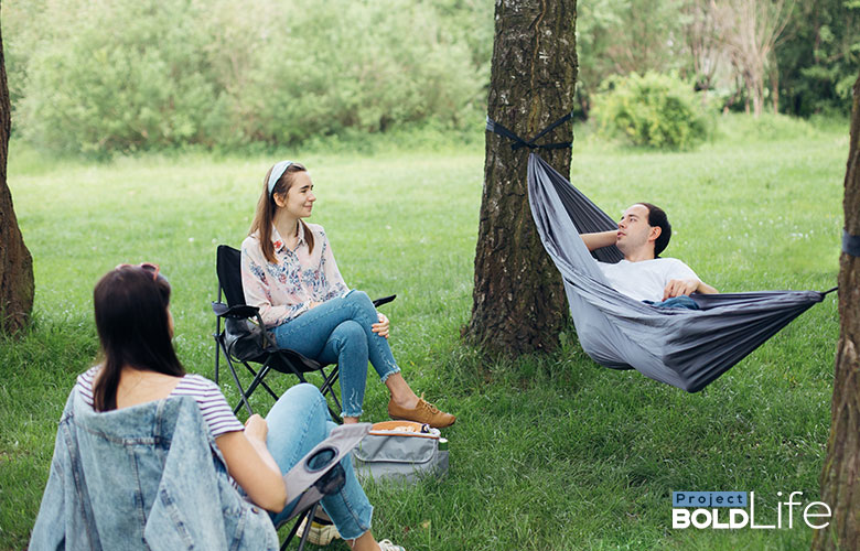 Some people chilling outside, talking to a dude in a hammock
