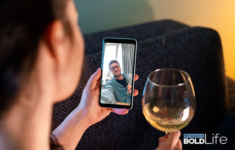 Someone drinking some white wine while having a digital date night