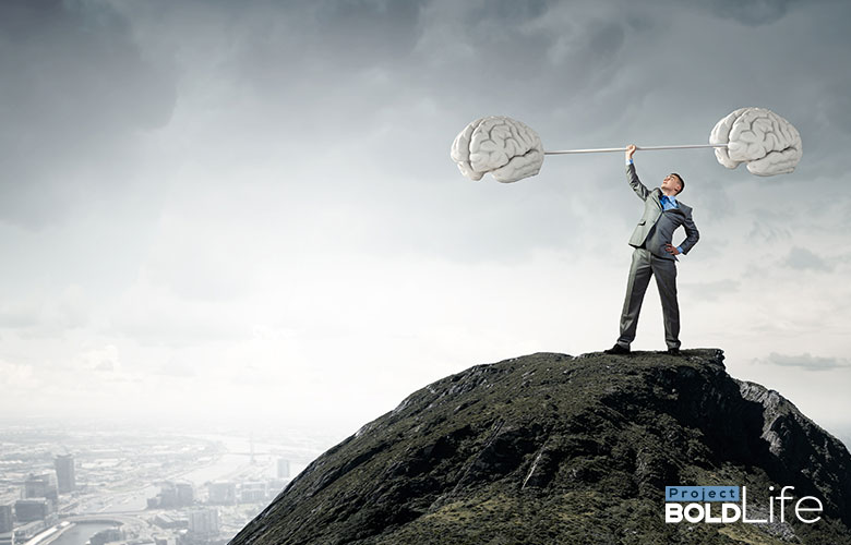 A person standing atop a mountain lifting a barbell with enlarged brains