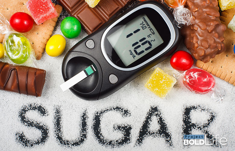 A ton of sugar and sweets around a blood sugar meter