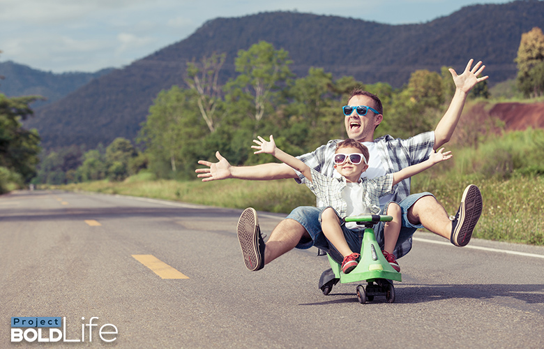 A dad and his kid driving down the highway in an illegal vehicle