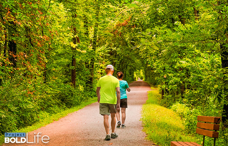 A couple power walking through the woods
