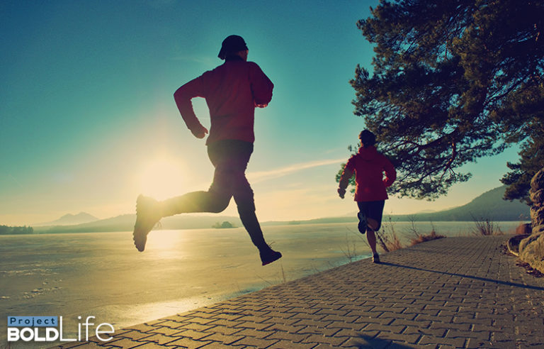 A couple running along the water reducing their stress