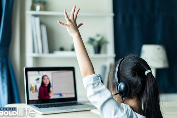 A kid learning from home and raising her hand