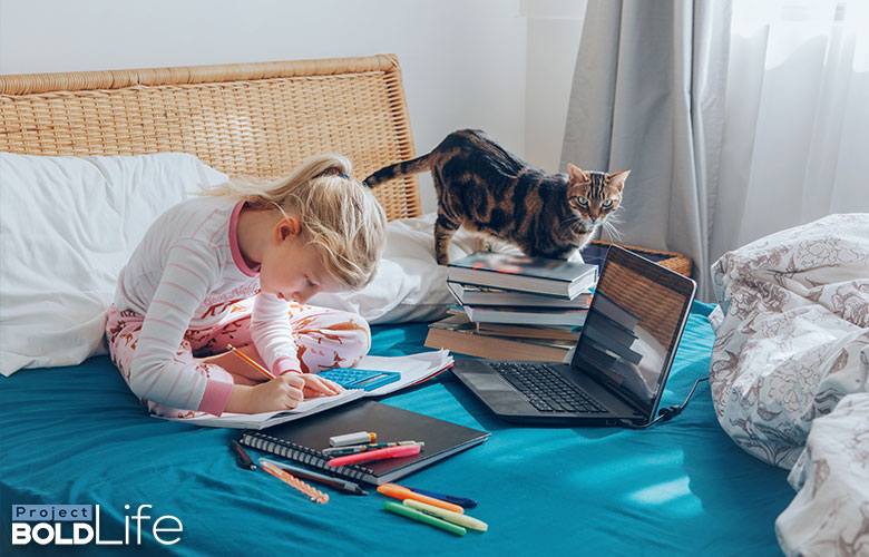 A kids learning from home with her cat as a teacher