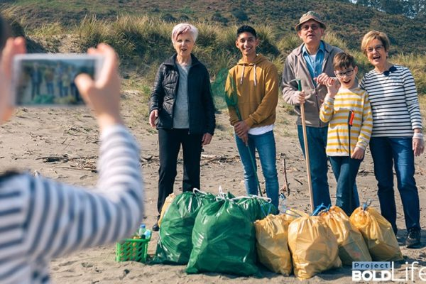 A family happily collecting trash on the beach