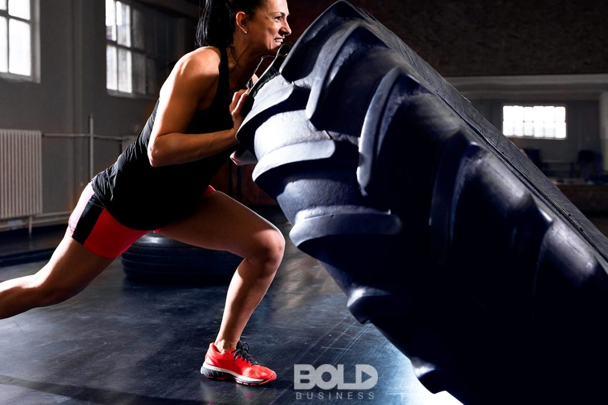 A woman flipping a tire in a hard workout