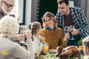 A family having a Thanksgiving dinner and drinking wine