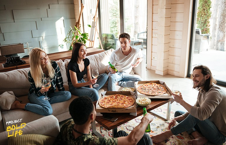 A group of people savoring free pizzas