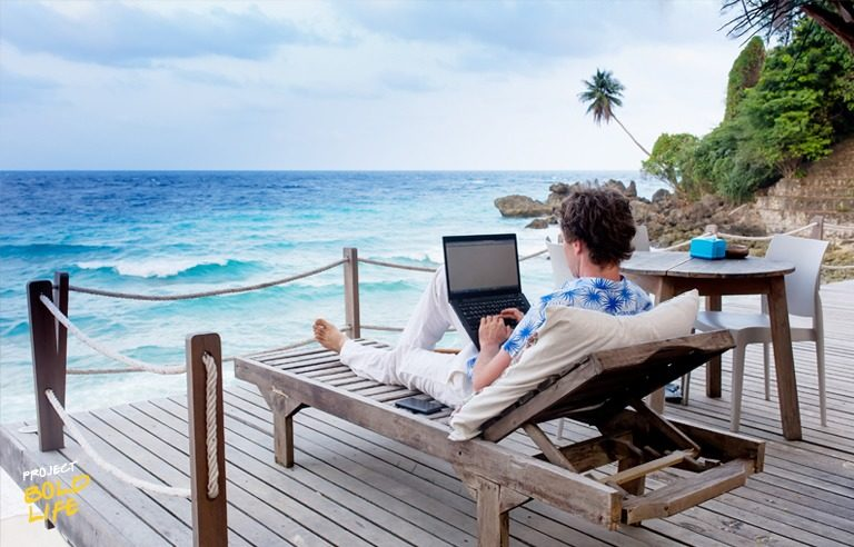 Some dude working on his laptop on the beach