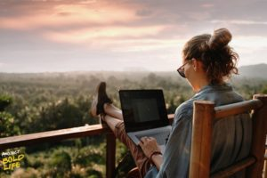 Some woman working on her laptop while looking out over nature