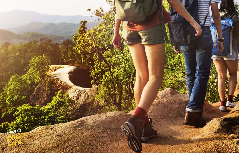 A group of hikers on a trail, from the torso down
