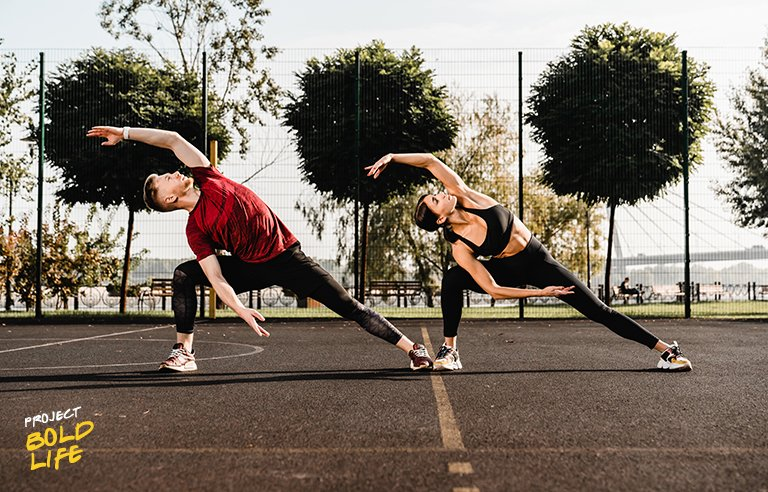 A couple doing side bends on a basketball court