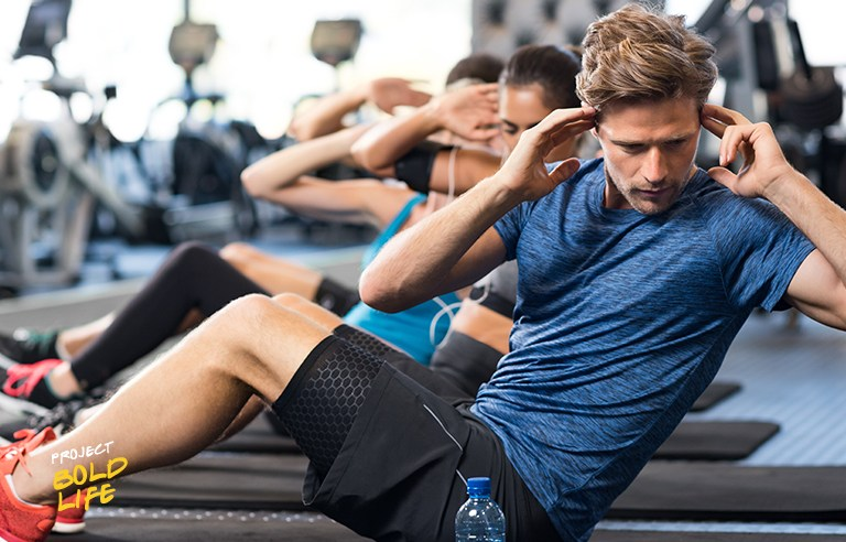 A dude doing situps in a gym with others