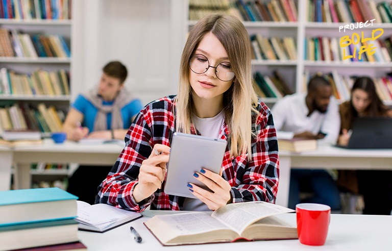 A college student wearing flannel in the library