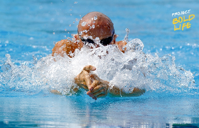 Some bald dude working his butterfly stroke